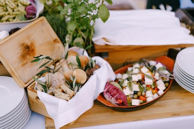 Houten kist met broodstengels en croutons op tafel met schone borden en salade