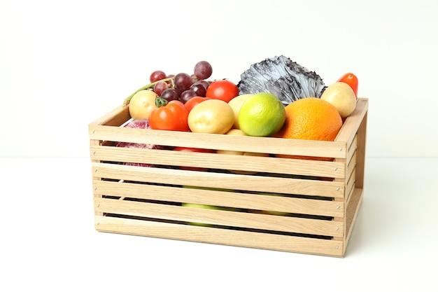 Houten kist met groenten en fruit op witte tafel
