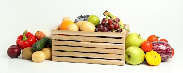 Houten kist met verschillende groenten en fruit op witte tafel