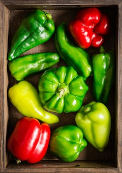 Houten kist met verschillende rode en groene paprika's close-up