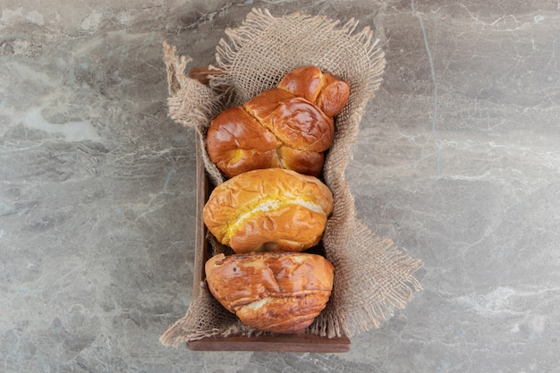 Houten kist met verschillende smakelijke gebakjes op marmeren backgroudn
