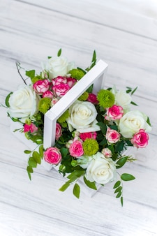 Houten kist met witte en roze rozen en chrysanten op wit houten bord. decoratie van huis. bloemen dozen. bruiloft decoratie