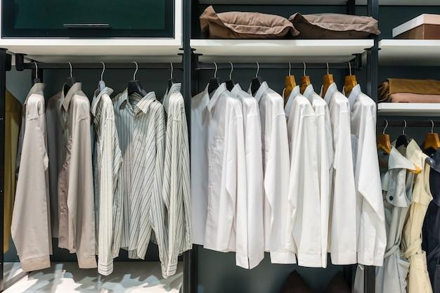 Houten kledingkast in inloopkast met kleding opknoping op spoor