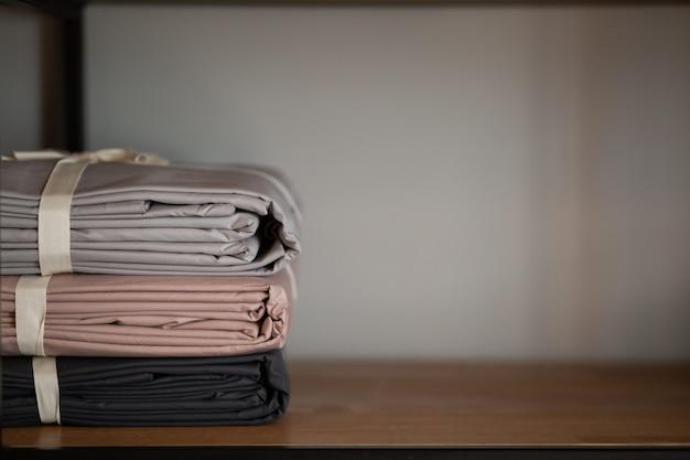 Houten kledingkast met beddengoed en kleding thuis of in een winkel, designconcept in het interieur