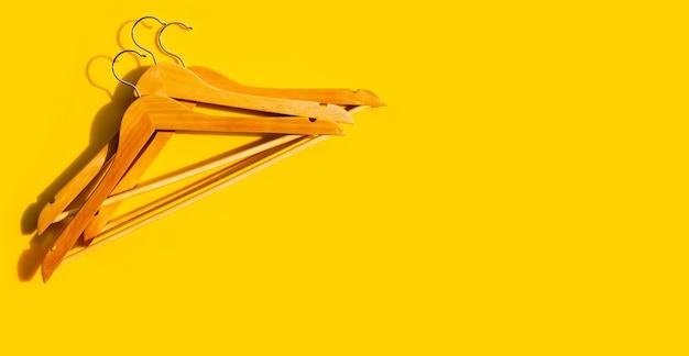 Houten kleerhangers op geel oppervlak