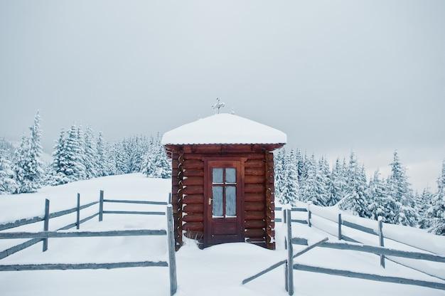 Houten kleine kerkkapel bij pijnbomen bedekt met sneeuw op berg chomiak, prachtige winterlandschappen van de karpaten, oekraïne, frost natuur,