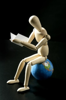 Houten kleine ledenpop die zitting over de wereldkaart danken