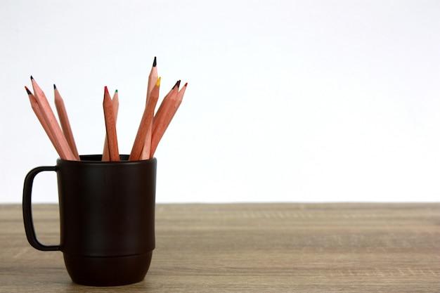Houten kleurpotlood in een houten kop op een houten lijst