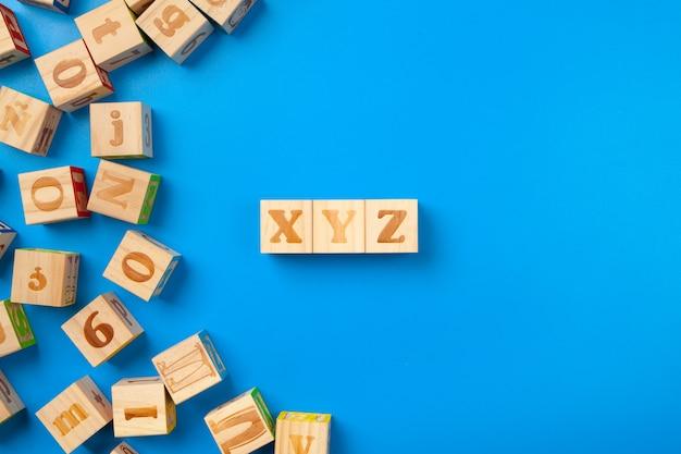 Houten kleurrijke alfabetblokken op blauw