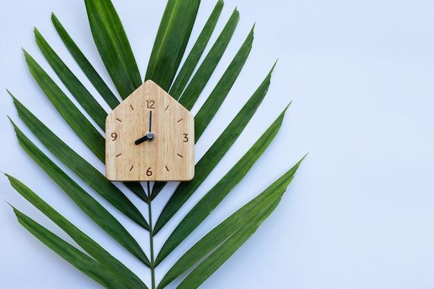 Houten klok op palmbladeren