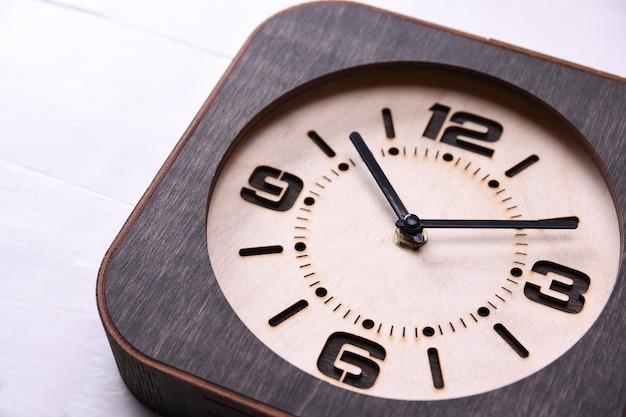 Houten klok ter beschikking gemaakt op houten tafel. detailopname. plaats voor een tekst.