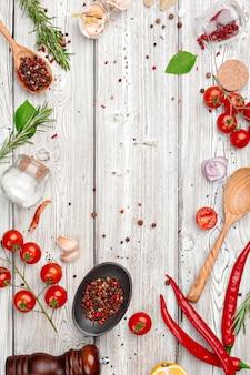 Houten koken achtergrond met verspreide kruiden en specerijen en kopie ruimte bovenaanzicht