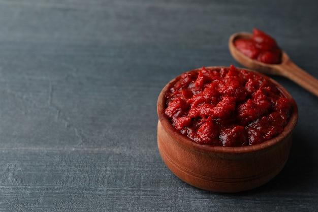 Houten kom en lepel met tomatenpuree op donkere houten oppervlakte