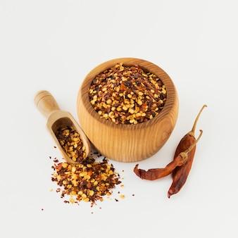 Houten kom en lepel vol gemalen rode cayennepeper, gedroogde chili vlokken en zaden geïsoleerd op een witte. zelfgemaakte kruideningrediënten om te koken.