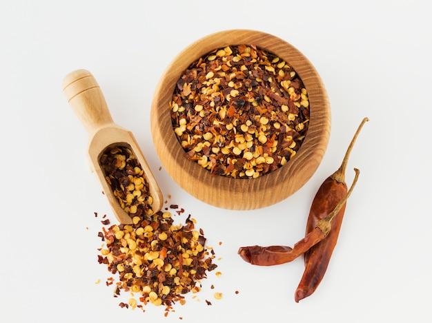 Houten kom en lepel vol gemalen rode cayennepeper, gedroogde chili vlokken en zaden geïsoleerd op een witte