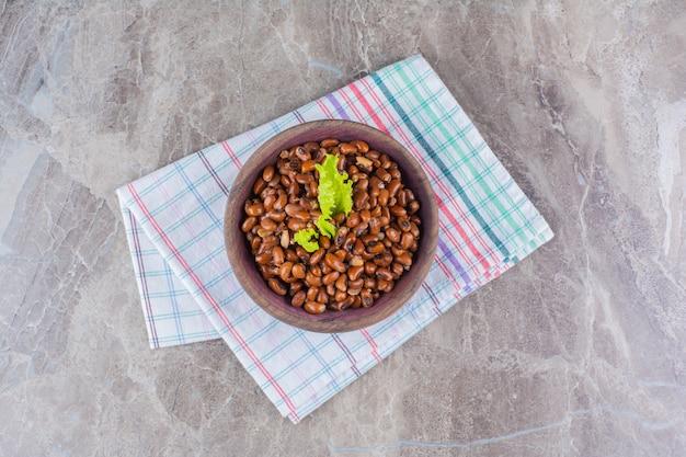 Houten kom gekookte bonen met tafelkleed op marmeren oppervlak.