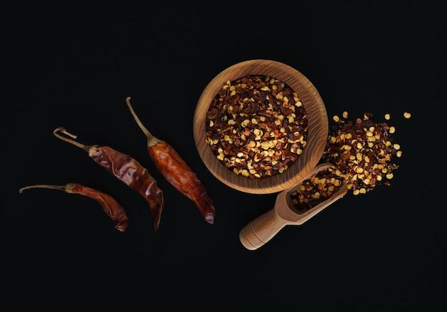 Houten kom gemalen rode cayennepeper, gedroogde chilivlokken en zaden op een zwarte achtergrond