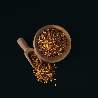 Houten kom gemalen rode cayennepeper, gedroogde chilivlokken en zaden op een zwarte. zelfgemaakte kruideningrediënten om te koken