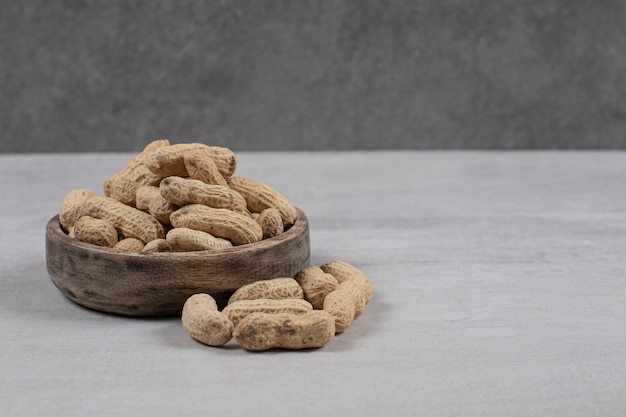 Houten kom gepelde pinda's op marmeren achtergrond.