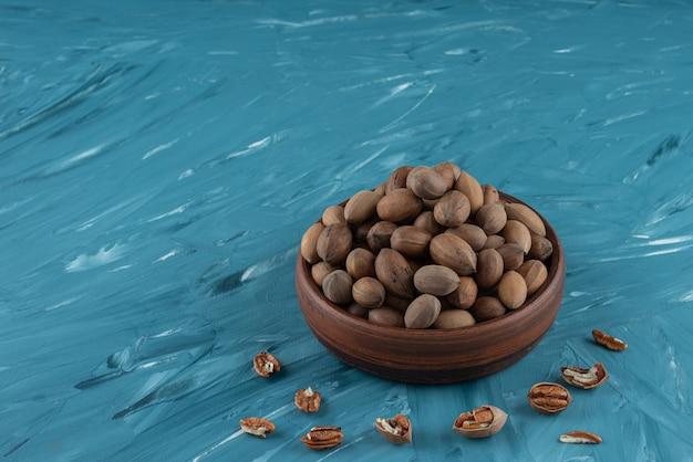 Houten kom geschilde biologische walnoten op blauwe ondergrond.