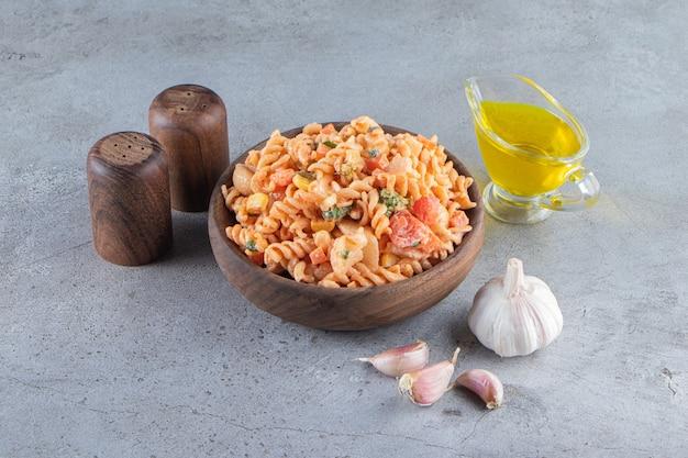 Houten kom heerlijke fusilli pasta op stenen achtergrond.