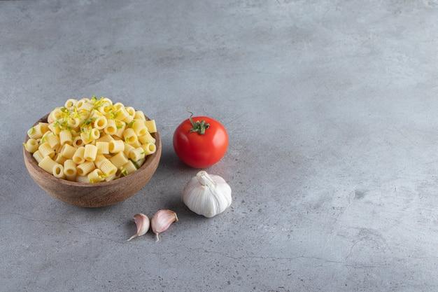 Houten kom heerlijke gekookte pasta op stenen achtergrond.