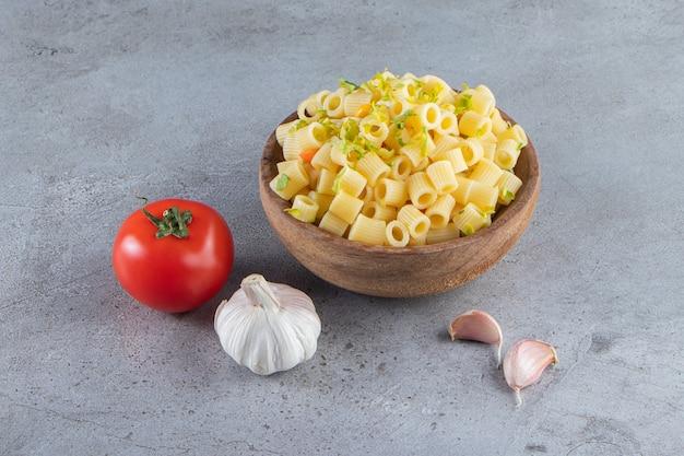 Houten kom heerlijke gekookte pasta op stenen oppervlak.
