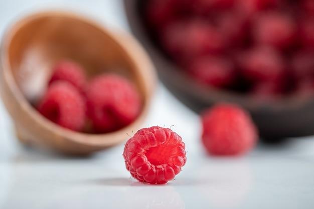 Houten kom heerlijke gezonde frambozen op stenen tafel