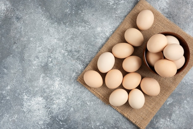 Houten kom met biologische rauwe eieren op marmeren oppervlak.