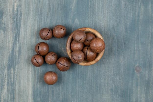Houten kom met chocoladeballen die op houten oppervlak worden geplaatst.