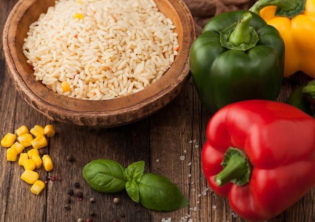 Houten kom met gekookte langkorrelige basmatirijst met groenten op houten tafelondergrond met paprikapeper met maïs en basilicum.