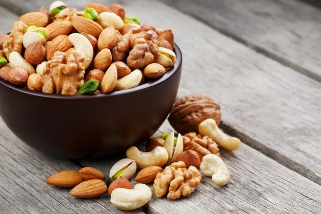 Houten kom met gemengde noten op houten grijs. walnoot, pistachenoten, amandelen, hazelnoten en cashewnoten, walnoot.