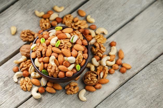 Houten kom met gemengde noten walnoot, pistachenoten, amandelen, hazelnoten en cashewnoten, walnoot.