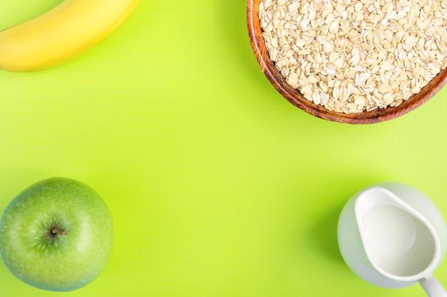 Houten kom met gerolde oates, witte kruik, melk, banaan groene appel op pistache achtergrond.
