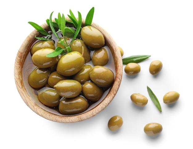 Houten kom met groene olijven op wit
