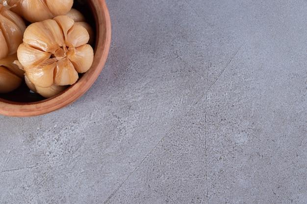 Houten kom met ingelegde knoflook die op steenlijst wordt geplaatst.