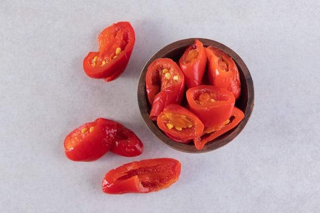 Houten kom met ingemaakte tomaten die op stenen tafel worden geplaatst.