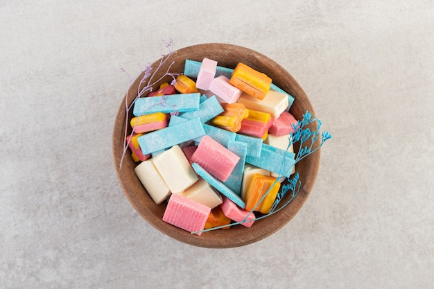 Houten kom met kleurrijke aromagommen op stenen tafel.