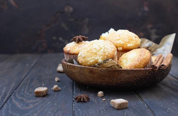 Houten kom met lekkere zelfgemaakte muffins, kaneel, anijsster en bruine suiker
