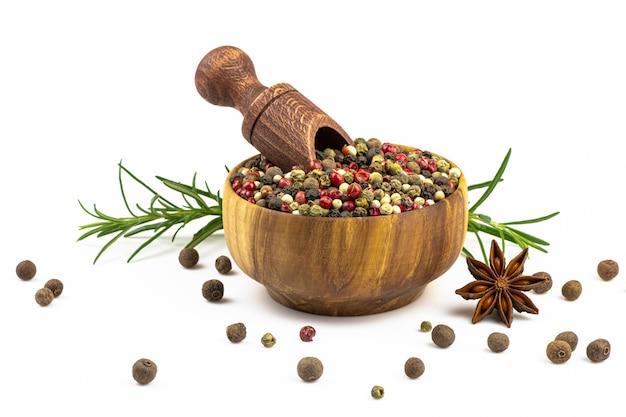 Houten kom met lepel en een mengsel van pepers, verspreide kruiden, rozemarijn geïsoleerd op een witte achtergrond.