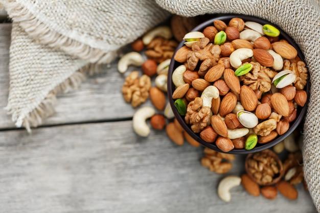 Houten kom met noten op een houten achtergrond, dichtbij een zak van jute.