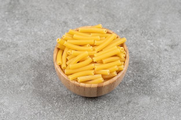 Houten kom met ongekookte macaroni op marmeren oppervlak
