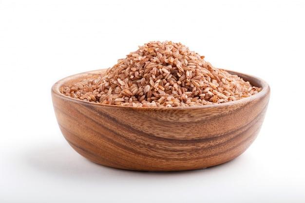 Houten kom met ongepolijste ongepelde rijst die op witte achtergrond wordt geïsoleerd