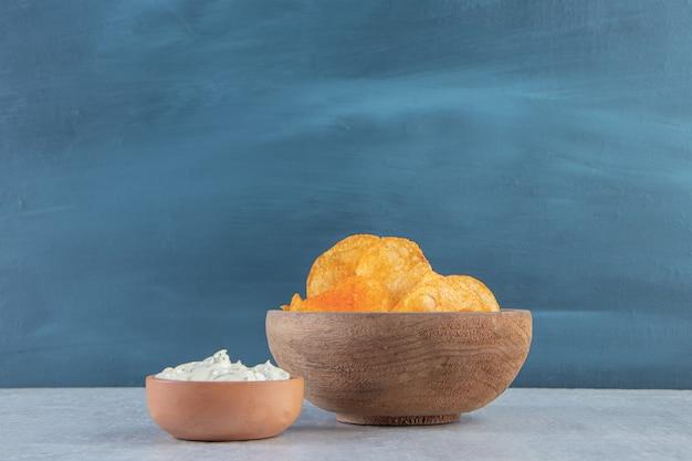 Houten kom met pittige chips en saus op steen.