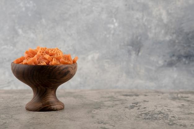 Houten kom met rauwe macaroni geplaatst op marmeren achtergrond