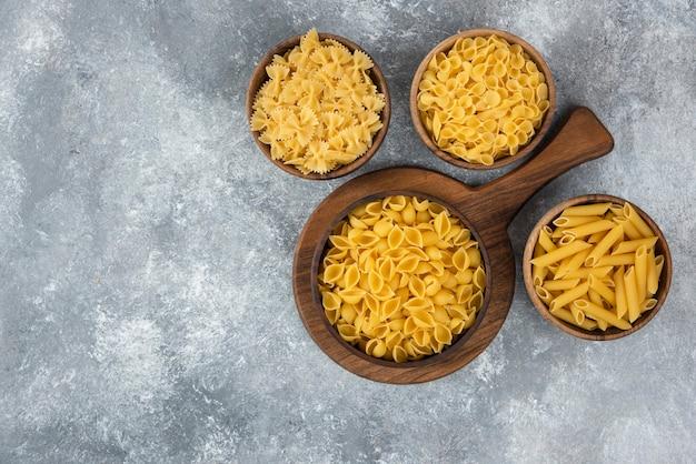 Houten kom met rauwe verschillende pasta op marmer.