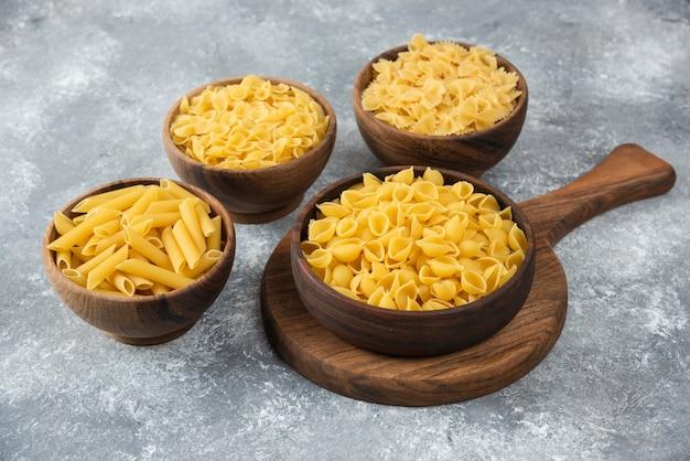 Houten kom met rauwe verschillende pasta op marmer. Gratis Foto
