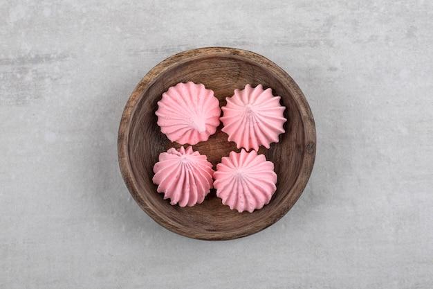 Houten kom met roze meringuesnoepjes op steen.