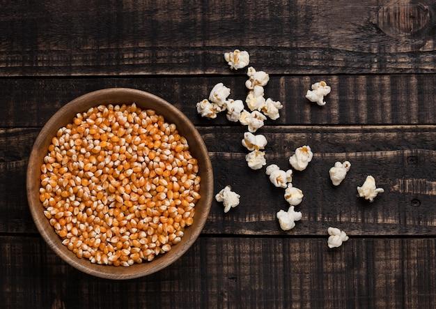 Houten kom met ruwe suikermaïs en popcorn op houten achtergrond