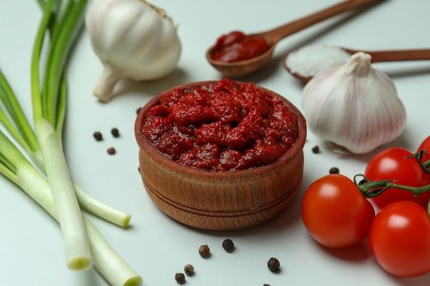 Houten kom met tomatenpuree en ingrediënten op witte achtergrond
